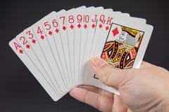 Una mano che tiene la serie dei diamanti dalle carte da gioco Fotografia Stock
