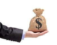 Una mano che tiene un sacchetto dei soldi Fotografie Stock Libere da Diritti