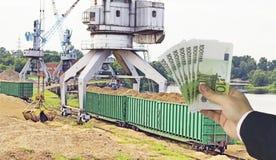 Una mano con el dinero euro contra una grúa del puerto hace el cargamento de pedazos de madera en los carros de la carga, exporta fotos de archivo