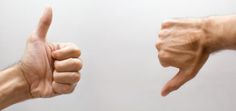 Una mano con el pulgar ascendente y un del pulgar abajo Fotografía de archivo libre de regalías