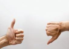 Una mano con el pulgar ascendente y un del pulgar abajo Imagen de archivo