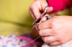 Una mano con il ditale che annoda e che taglia un filo su un ago in una sessione di cucito immagine stock
