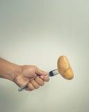 Una mano con la patata e la forcella Fotografie Stock Libere da Diritti