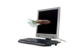 Una mano con mucho dinero fuera de un monit del ordenador Foto de archivo