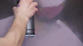 Una mano con una poder de espray que dibuja una nueva pintada en la pared Foto del proceso de dibujar una pintada en un de madera metrajes