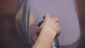 Una mano con una poder de espray que dibuja una nueva pintada en la pared Foto del proceso de dibujar una pintada en un de madera Fotografía de archivo libre de regalías