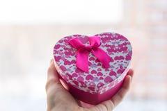 Una mano con un regalo de la caja Imagen de archivo