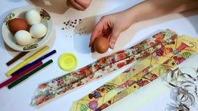 Una mano de la hembra sostiene un huevo marrón, y un niño pega un ojo a él Decoración para el día de fiesta de Pascua