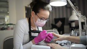 Una mano de la manicura con mentiras del clavo en la mano de un manicuro en guantes higiénicos rosados El amo hace francés de la  almacen de metraje de vídeo