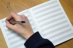 Una mano de la mujer escribió en las notas de papel, triple Imagen de archivo