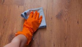 Una mano de la mujer usando los trapos azules limpia el piso de madera Foto de archivo libre de regalías