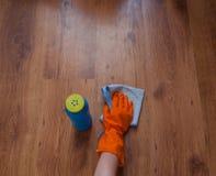 Una mano de la mujer usando los trapos azules limpia el piso de madera Foto de archivo