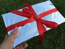 Una mano de la señora está sosteniendo una caja de regalo foto de archivo
