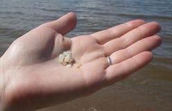 Una mano de las piedras de la arena de la explotación agrícola de la mujer Foto de archivo libre de regalías
