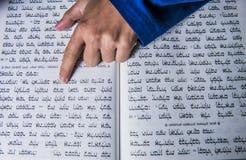 Una mano de los rezos en una biblia judía Fotos de archivo libres de regalías