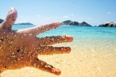 Una mano de un hombre en la playa imagen de archivo