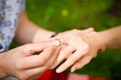 Una mano de un hombre que pone un anillo en el dedo de una muchacha Fotos de archivo