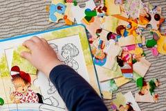 Una mano del bambino con il puzzle Fotografia Stock