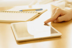 Una mano del estudiante que busca en una tableta en un escritorio en ho Imágenes de archivo libres de regalías
