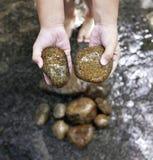 Una mano del niño con una piedra imagenes de archivo