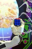 Una mano del robot che tiene un cubo del ` s di Rubik con i precedenti astratti Immagine Stock Libera da Diritti
