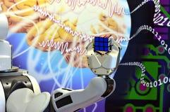 Una mano del robot che tiene un cubo del ` s di Rubik con i precedenti astratti Fotografia Stock