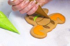 Una mano del ` s de la mujer adorna el pan de jengibre hecho a mano de la Navidad con el esmalte Galletas bajo la forma de figura Fotografía de archivo libre de regalías