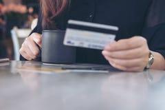 Una mano del ` s de la mujer que sostiene tarjetas de crédito y la taza del café sólo en la tabla Imagen de archivo
