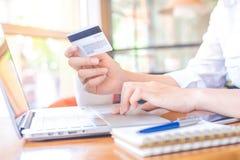Una mano del ` s de la mujer sostiene una tarjeta de crédito y utiliza un ordenador portátil Imagen de archivo