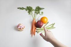 Una mano del ` s de la persona que alcanza para las frutas y verduras en vez de a Foto de archivo libre de regalías