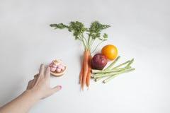 Una mano del ` s de la persona que alcanza para una magdalena en vez de las frutas y de Veg Foto de archivo libre de regalías