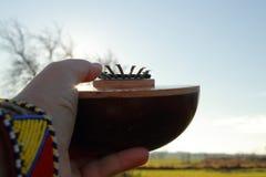 Una mano del ` s dell'uomo bianco con un braccialetto a mano decorato piacevole tiene il calimba africano tradizionale dello stru Fotografia Stock Libera da Diritti