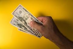 Una mano del ` s dell'uomo dà i dollari Mano e soldi su un fondo giallo Fotografia Stock