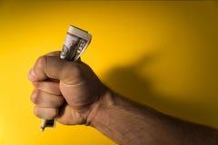 Una mano del ` s dell'uomo dà i dollari Mano e soldi su un fondo giallo Mancanza di fondi Bilancio familiare Fotografia Stock Libera da Diritti