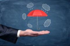 Una mano del ` s dell'uomo d'affari girata su e un piccolo ombrello rosso che si libra sopra sul fondo della lavagna Fotografia Stock Libera da Diritti