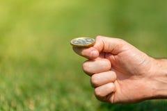 Una mano del ` s dell'uomo getta un bitcoin della moneta di oro Fotografia Stock Libera da Diritti