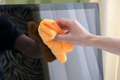 Una mano del ` s dell'uomo pulisce il monitor con un panno da polvere Fotografia Stock Libera da Diritti