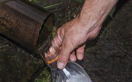Una mano del ` s dell'uomo tiene una bottiglia di plastica e versa l'acqua da Fotografie Stock