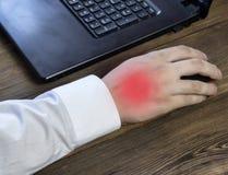 Una mano del ` s dell'uomo tiene un topo mentre lavora ad un computer, un dolore in sua mano, un primo piano immagini stock