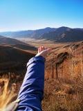 Una mano del ` s della donna allungata alla bellezza delle montagne Fotografia Stock