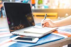 Una mano del ` s della donna che lavora ad un computer portatile e che scrive su una n Fotografia Stock