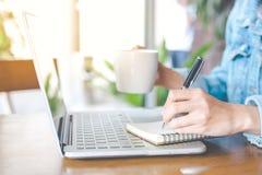 Una mano del ` s della donna che lavora ad un computer portatile e che scrive su una n Fotografia Stock Libera da Diritti