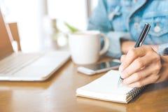 Una mano del ` s della donna che lavora ad un computer portatile e che scrive su una n Fotografie Stock Libere da Diritti