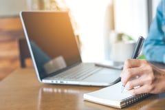 Una mano del ` s della donna che lavora ad un computer portatile e che scrive su una n Fotografie Stock
