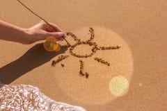 Una mano del ` s della donna estrae il sole sulla sabbia dal mare, l'effetto di incandescenza Immagini Stock Libere da Diritti