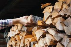 Una mano del ` s della donna prende ad una betulla il ceppo scheggiato asciutto da una catasta di legna immagine stock libera da diritti