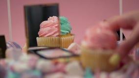 Una mano del ` s della donna prende un muffin con crema rosa stock footage