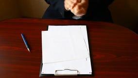 Una mano del ` s del hombre arruga la hoja del papel en blanco, lanza esto en la tabla metrajes