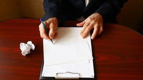 Una mano del ` s del hombre arruga la hoja del papel en blanco, lanza esto en la tabla almacen de metraje de vídeo