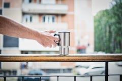 Una mano del ` s del hombre con un termo asalta en el balcón Fotos de archivo